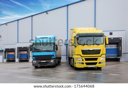 Trucks in warehouse building - stock photo