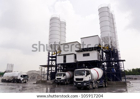 Trucks loading at a Concrete mixing factory. - stock photo