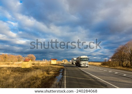 Trucks moving by the road under a beautiful autumn cloudy sky  - stock photo