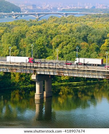 Trucks on a bridge over the river. Kiev, Ukraine - stock photo