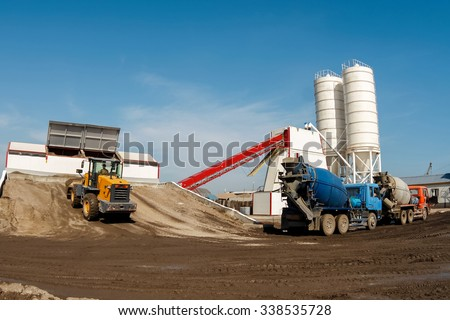 Trucks waiting to fill the concrete factory. - stock photo