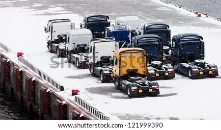Trucks waits on snowbound pier in port - stock photo