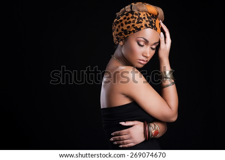 True African beauty. Beautiful African woman wearing a headscarf and posing against black background - stock photo