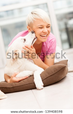 true friendship between human and dog who is giving a kiss to her - stock photo