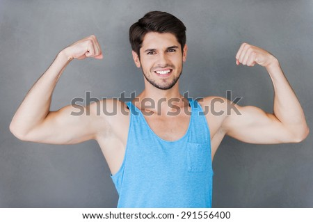True masculinity. Handsome young muscular man showing his perfect biceps while standing against grey background - stock photo