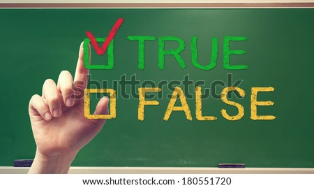 TRUE or FALSE checkbox with hand on green chalkboard - stock photo