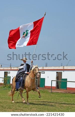 TRUJILLO, PERU - SEPTEMBER 1, 2014: Man riding a Peruvian Paso horse and carrying large flag of Peru on a long pole in Trujillo, Peru. - stock photo
