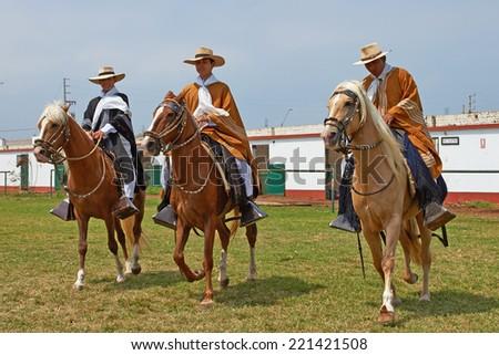 TRUJILLO, PERU - SEPTEMBER 1, 2014: Peruvian Paso horses being ridden by men in traditional clothing in Trujillo, Peru - stock photo