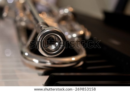 Trumpet segment closeup lying on piano keys - stock photo