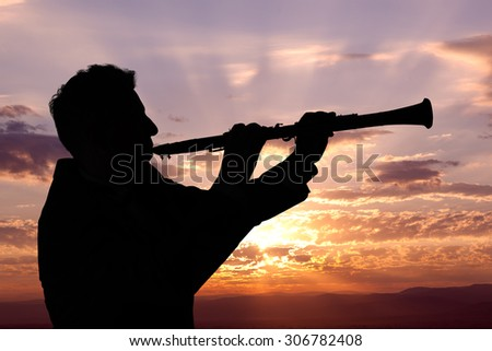 Trumpeter. Man playing on oboe against the background of sunset - stock photo
