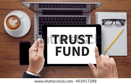 TRUST FUND , on the tablet pc screen held by businessman hands - online, top view - stock photo