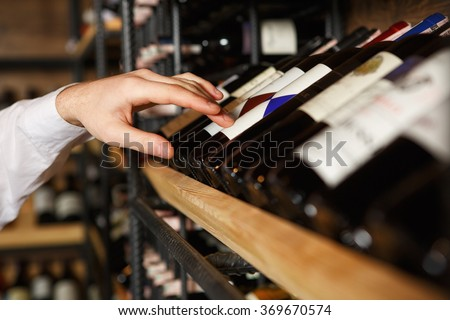 Trust him with the choice. Closeup shot of a sommelier choosing a wine bottle from the shelf in a wine cellar - stock photo