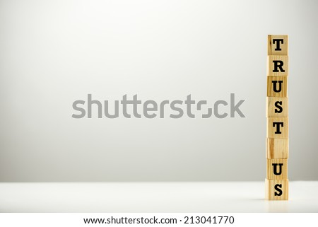 Trust Us concept with the alphabet letters spelling the words arranged on a stacked tower of wooden blocks or cubes on the right of the frame with copyspace for your text or advertising. - stock photo