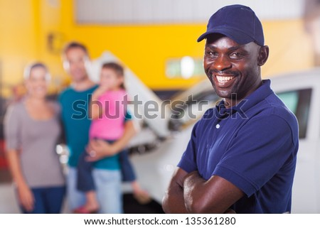 trustworthy african auto mechanic standing in front of family inside garage - stock photo