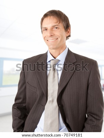 Trustworthy mature businessman portrait in an office environment, smiling