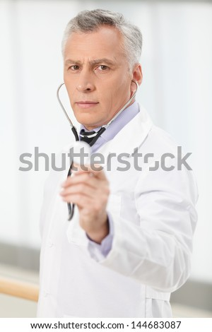 Trustworthy medical doctor. Confident mature doctor holding a stethoscope in his outstretched hand