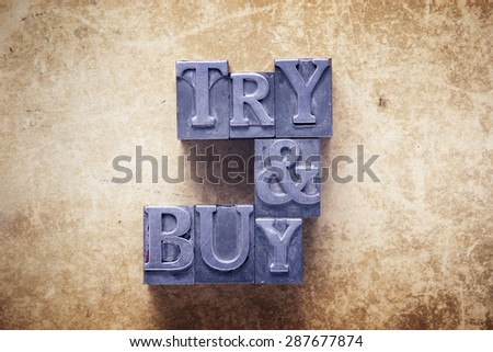 try and buy slogan made from metallic letterpress type on vintage cardboard - stock photo
