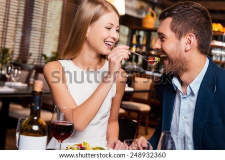 Try my meal! Beautiful young loving couple enjoying dinner at the restaurant while woman feeding her boyfriend with salad - stock photo
