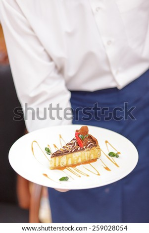 Try our tasty specials. Closeup shot of exquisite dessert on the plate in hands of waiter in uniform in the luxury restaurant - stock photo