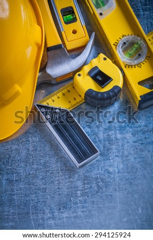 Try square construction level tape-measure protective helmet and claw hammer on metallic background vertical version maintenance concept.
