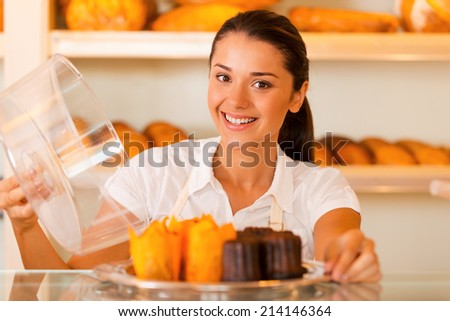 Try this! Attractive young woman in apron carrying plate with fresh cookies and smiling while standing in bakery shop - stock photo