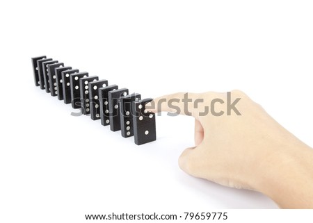 try to fall dominos, dominos arranging in line and hand try to fall down. - stock photo