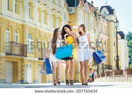 Trying new dress near shop. Three attractive young girl holding shopping bags while walking outdoors laughing and smiling. - stock photo