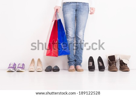 Trying on Shoes. Woman stands in a pair of open toe shoes with many other options on the floor - stock photo