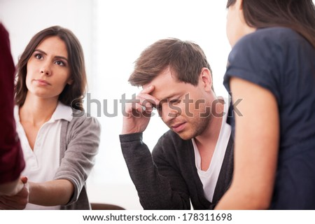 Trying to stay strong. Depressed young man sitting at the chair and holding head in hand while other people sitting around him  - stock photo