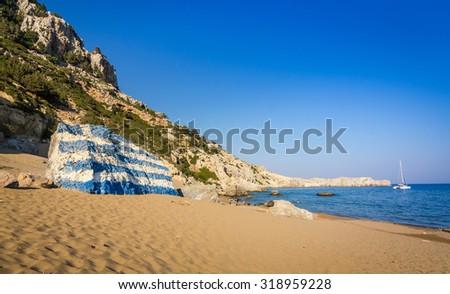 Tsambika beach landscape with Greece flag - stock photo