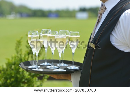 TSELEEVO, MOSCOW REGION, RUSSIA - JULY 26, 2014: Waiter holds the tray with champagne for the guests of the British Polo Day. It was the second British Polo Day in Russia - stock photo
