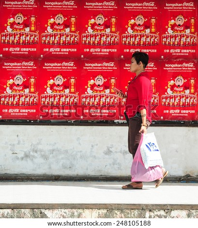 Tuaran Sabah Malaysia - January 29, 2015 : Unidentified woman pass by a Coca-Cola poster for Chinese New Year 2015 festival at Pekan Tuaran. Lunar New Year of the Goat will fall on February 19,2015. - stock photo