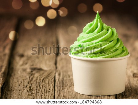 Tub of twirling creamy green Italian ice cream on a rustic wood table with a sparkling bokeh of party lights - stock photo
