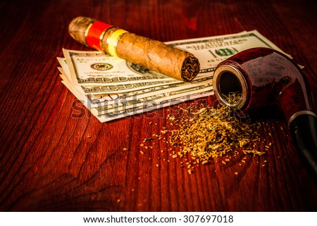 Tube for smoking tobacco and money with cuban cigar on a wooden table. Focus on the tube, image vignetting and hard tones - stock photo