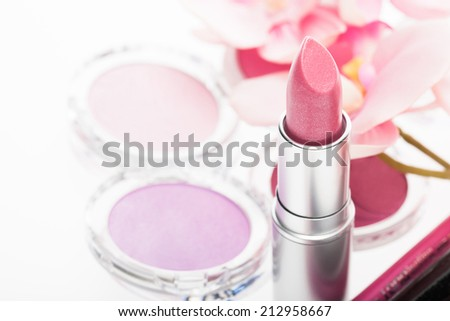 Tube of pretty pink lipstick with matching eye shadow and blusher in a beauty background with focus to the lipstick