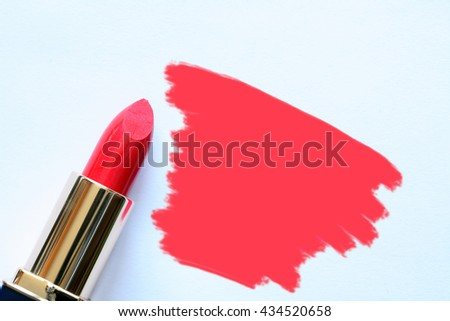 Tube of red lipstick near abstract spot on white background - stock photo