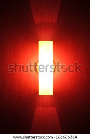 Tube of red neon light on textured wall - stock photo