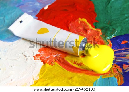 Tube of yellow paint on the color palette  - stock photo