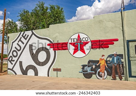 TUCUMCARI, NEW MEXICO - AUGUST 25, 2013: Photo of a mural showing an old Chrysler, the Texaco logo, a Route 66 sign, a woman, and a cowboy on the side of a building
