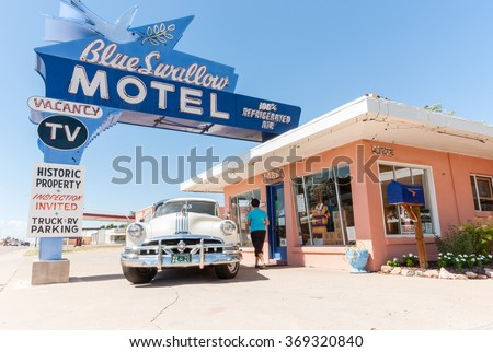TUCUMCARI, NEW MEXICO, USA - SEPTEMBER 14; Tourist in blue top walks up to lobby door of Blue Swallow Motel on September 14, 2015 at Tucumcari, Route 66 New Mexico USA.