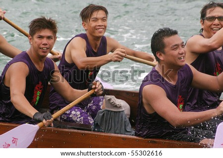 TUEN MUN, HONG KONG -  JUNE 16: Participants smile as they paddle their boats during a dragon boat race on June 16, 2010 in Tuen Mun, Hong Kong - stock photo