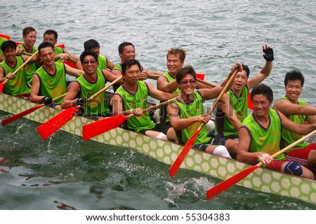 TUEN MUN, HONG KONG -  JUNE 16: Participants smile while paddling their boat during a dragon boat race on June 16, 2010 in Tuen Mun, Hong Kong - stock photo