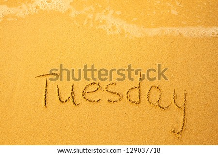 Tuesday - written in sand on beach texture - soft wave of the sea (days week series) - stock photo