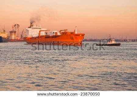 Tug and tanker on the river in orange sunset - stock photo