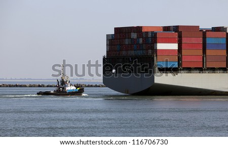 tug behind a containership - stock photo