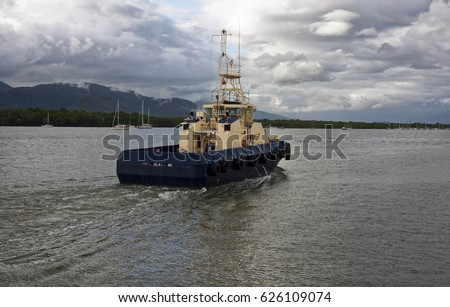 tug boat coming into Cairns harbor on a cloudy day