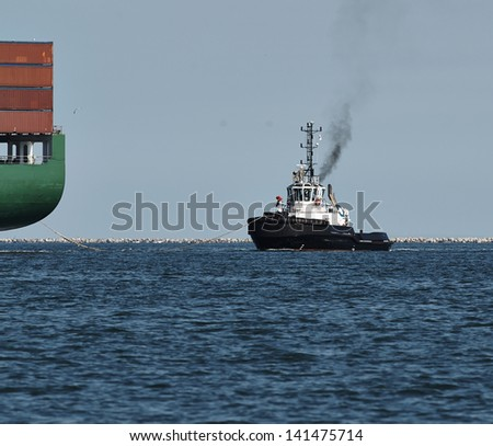 tug boat iowing a big container ship - stock photo