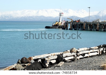 Tug boat moving past the ferry dock on a sunny day at the harbor in Homer Alaska - stock photo