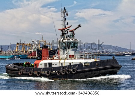 tug boat working in harbor with shipping in the background - stock photo