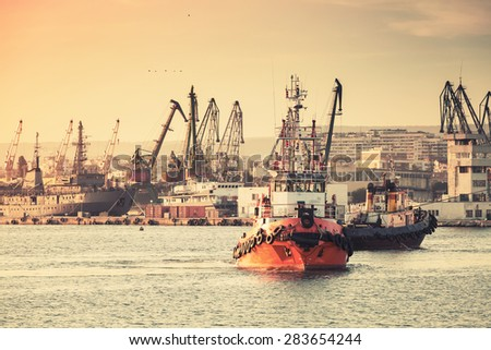 Tug boats are working in Varna harbor. Black Sea, Bulgaria. Vintage stylized photo with warm tonal correction photo filter, instagram old style  - stock photo